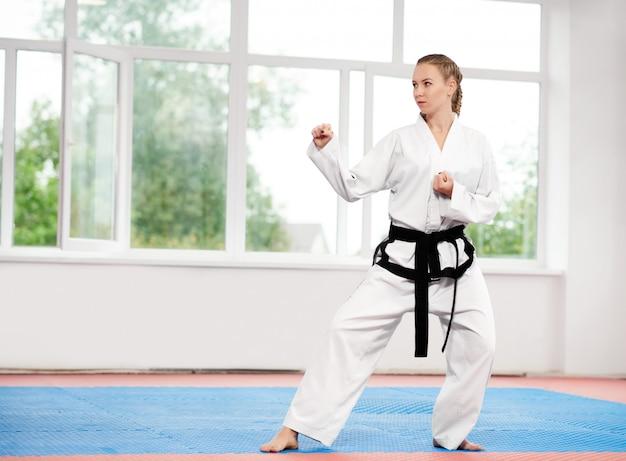 Mulher desportiva de karatê e taekwondo no quimono branco com faixa preta.