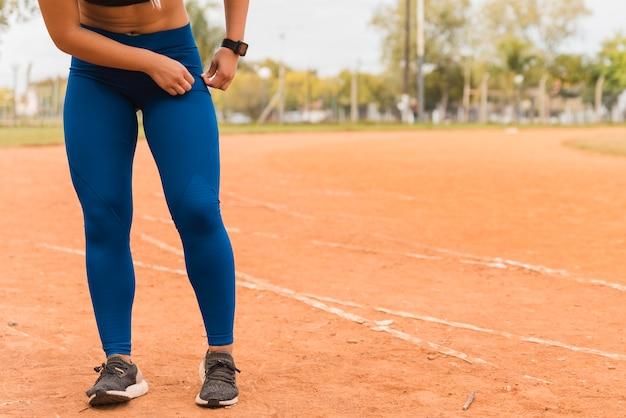 Mulher desportiva de pé na pista do estádio