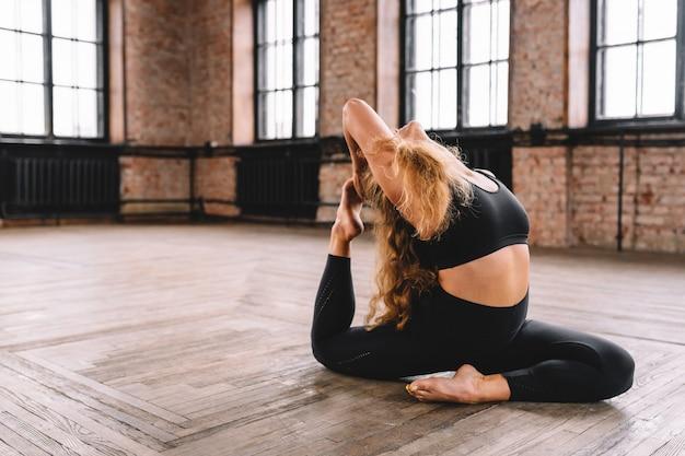 Mulher desportiva de yogini em forma fazendo ioga asana eka pada kapotasana - pose de pombo de uma perna só na aula de estilo loft.