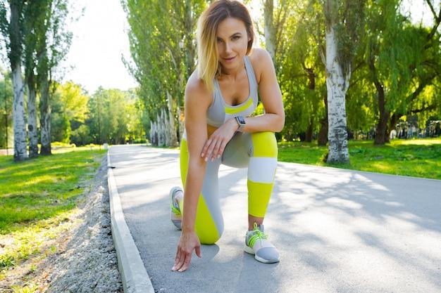 Mulher desportiva em execução começar pose no parque da cidade