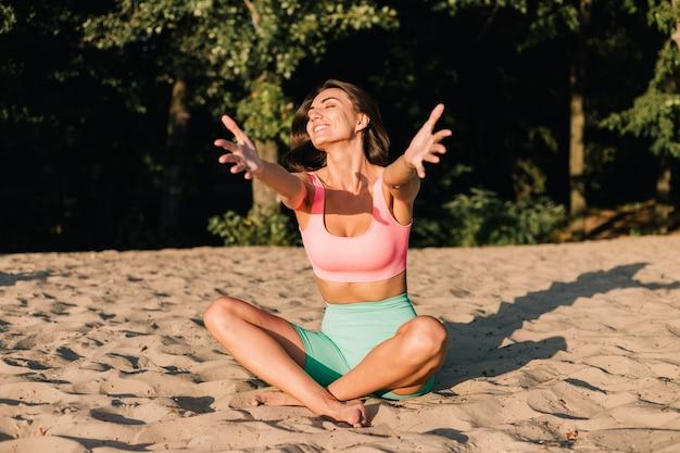 Mulher desportiva em forma perfeita ao pôr do sol na praia em pose de ioga calma