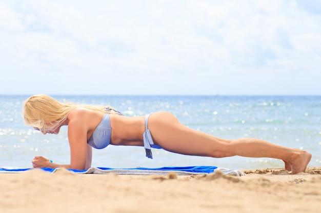 Mulher desportiva em posição de prancha na praia. um estilo de vida saudável.