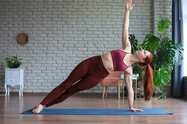 Mulher desportiva em roupas esportivas praticando ioga, malhando em casa ou no estúdio de ioga.