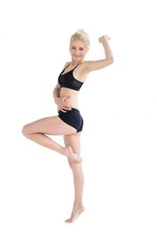 Mulher desportiva, equilibrando-se em uma perna enquanto estendendo a mão