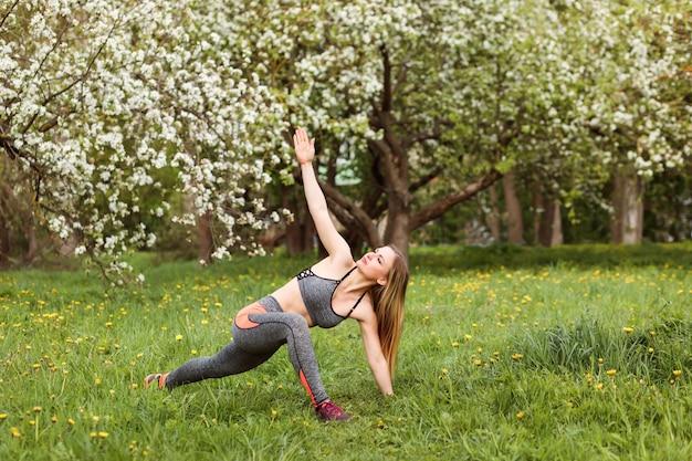 Mulher desportiva está se exercitando no jardim florido na primavera.