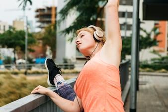 Mulher desportiva, estendendo-se em ambiente urbano