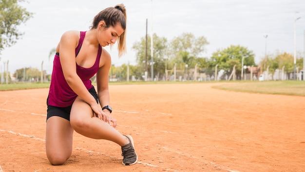 Mulher desportiva, estendendo-se na pista do estádio