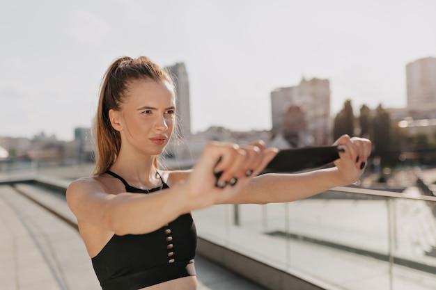 Mulher desportiva esticando os braços e olhando concentrada ao ar livre na cidade