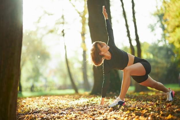 Mulher desportiva fazendo exercícios de fitness no parque local