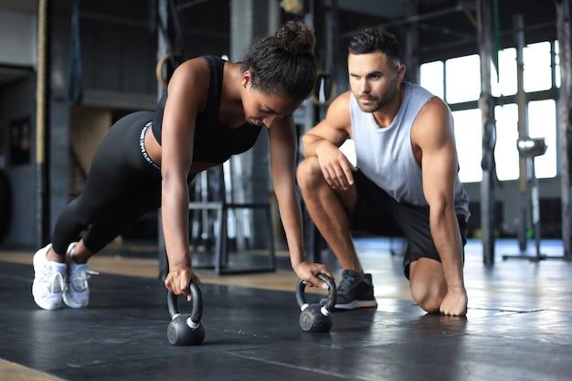 Mulher desportiva fazendo flexões em uma academia, o namorado dela está olhando para ela.