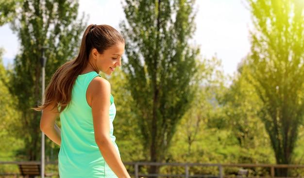 Mulher desportiva feliz linda dinâmica olhando para o lado. garota fitness, desfrutando de seu treino no parque. copie o espaço.