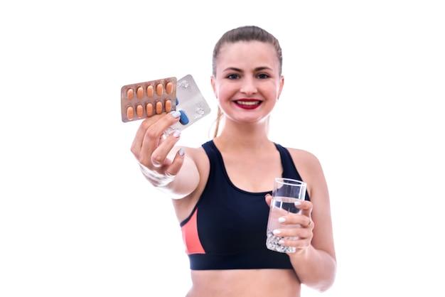 Mulher desportiva feliz segurando bolhas com comprimidos e um copo de água