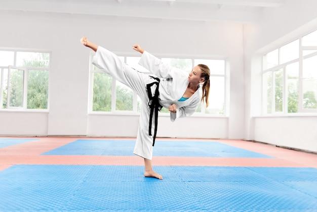 Mulher desportiva karatê contra grande janela em pé na posição de karatê.