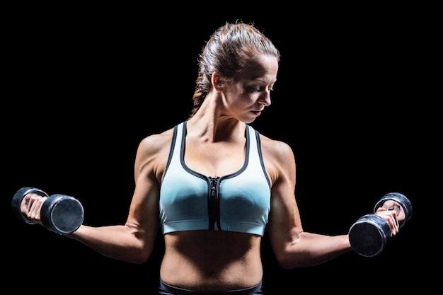 Mulher desportiva levantando dumbbells