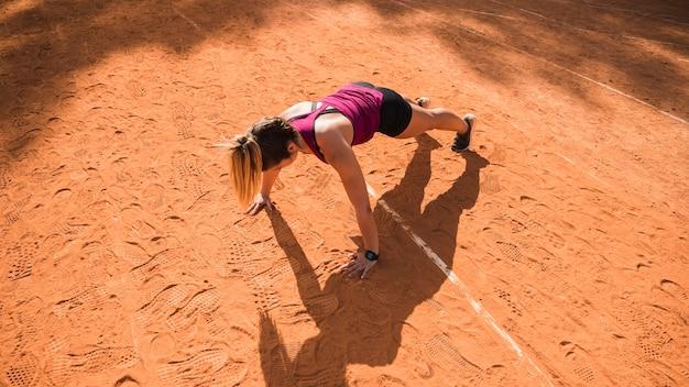 Mulher desportiva malhando na pista do estádio