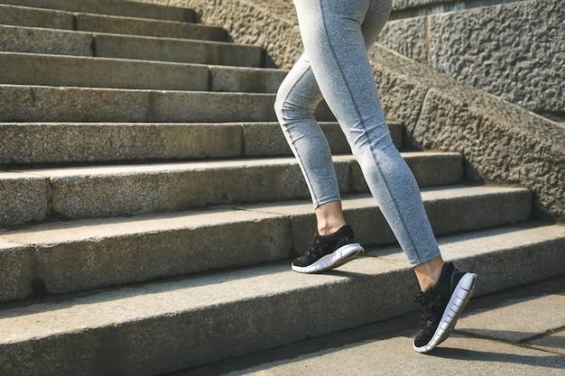 Mulher desportiva malhando subindo escadas ao ar livre para o treino matinal