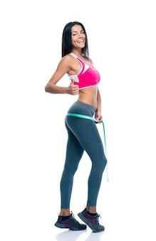 Mulher desportiva mede as nádegas com uma fita métrica