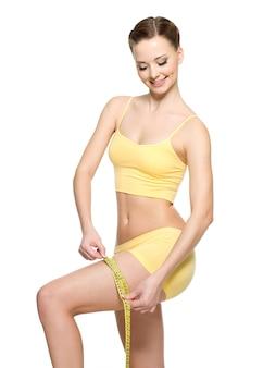 Mulher desportiva medindo o quadril com fita adesiva após o treino - isolado no branco