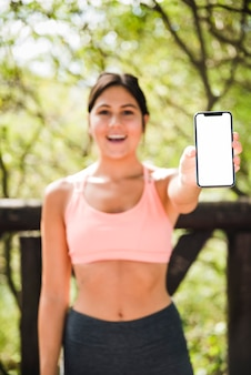 Mulher desportiva mostrando modelo de smartphone ao ar livre