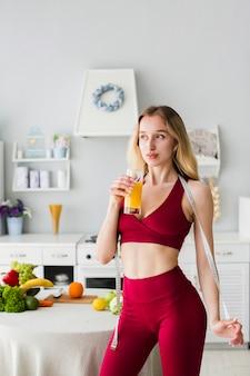 Mulher desportiva na cozinha com suco saudável