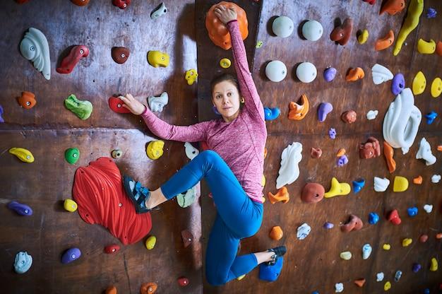 Mulher desportiva na sala de escalada em pedregulho. comprimento total