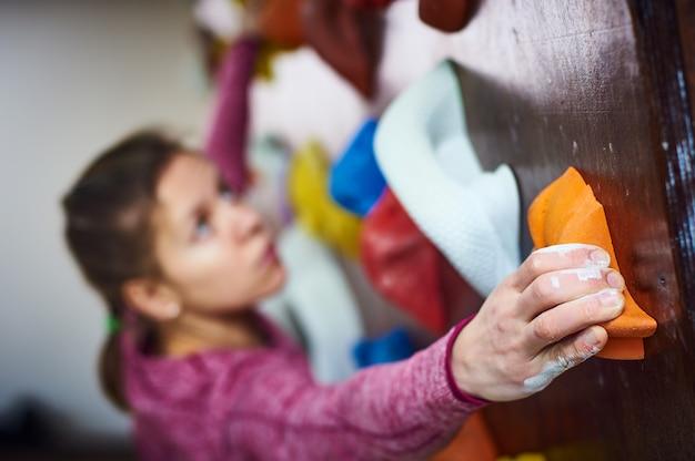 Mulher desportiva na sala de escalada em pedregulho. foco em uma mão