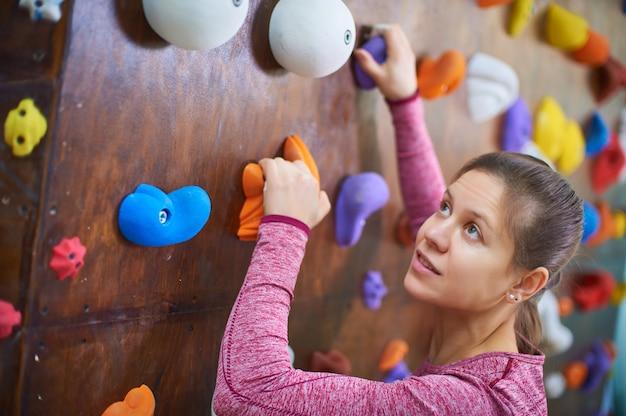 Mulher desportiva na sala de escalada em pedregulho