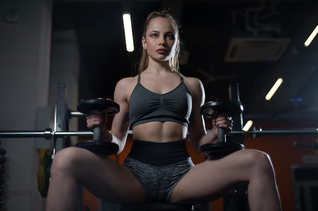 Mulher desportiva no sportswear descansando no banco segurando halteres nas mãos no ginásio
