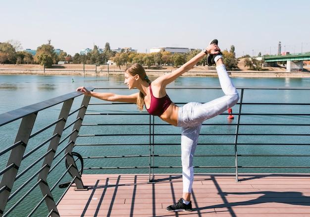 Mulher desportiva nova que estica em uma perna que está sobre a ponte