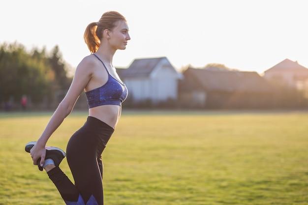 Mulher desportiva nova que faz o exercício antes de correr no campo da manhã ao ar livre.