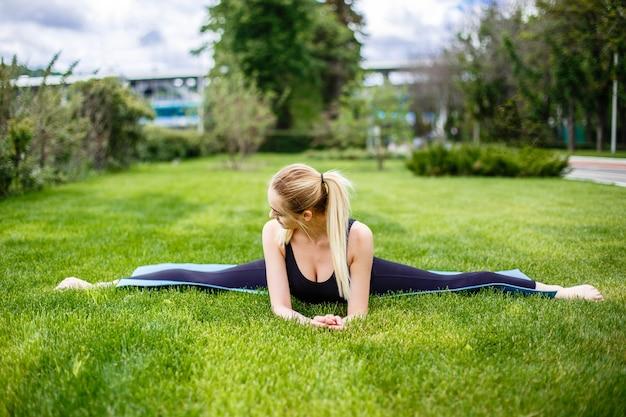 Mulher desportiva nova que senta-se na grama no parque, separações ginásticas.