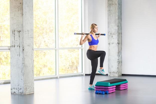 Mulher desportiva pratica na plataforma de degraus. foto de estúdio