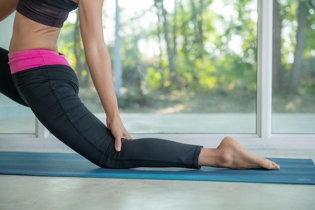 Mulher desportiva praticando ioga, fazendo exercícios de cavaleiro, pose de anjaneyasana, malhando, vestindo roupas esportivas, calças pretas, fazendo exercícios em casa sentado.