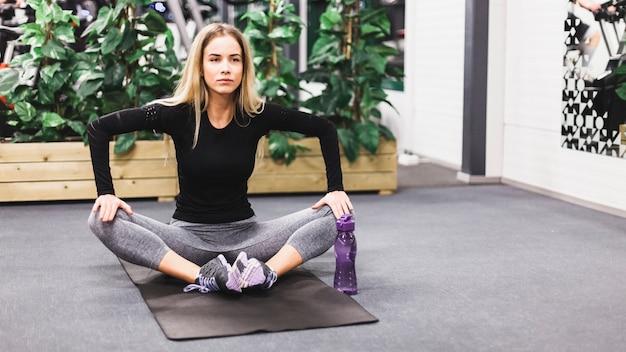 Mulher desportiva praticando ioga na esteira de exercícios