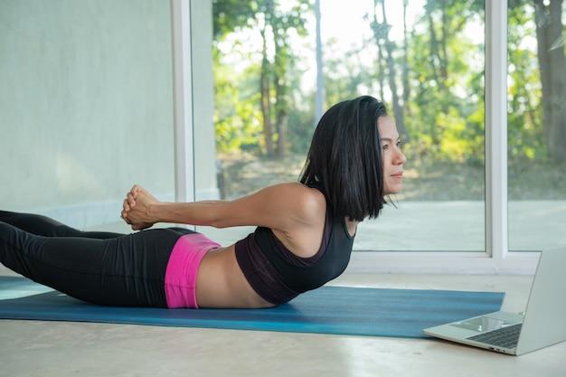 Mulher desportiva praticando ioga, pose de treino de costas e nádegas, alongamento, assistindo a um vídeo tutorial de fitness online no laptop, fazendo exercícios em casa sentada na esteira na sala de estar praticando