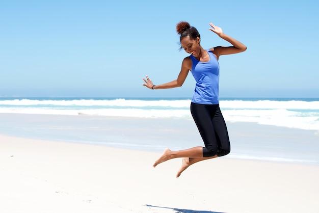 Mulher desportiva pulando na praia