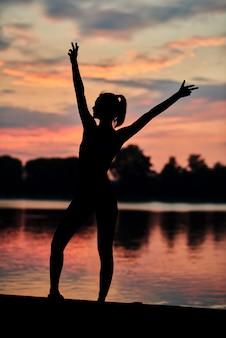 Mulher desportiva que levanta perto do lago da cidade no por do sol