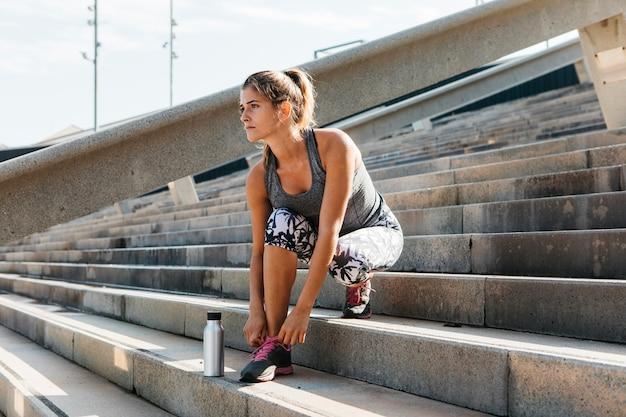 Mulher desportiva, sapatos de fixação em ambiente urbano