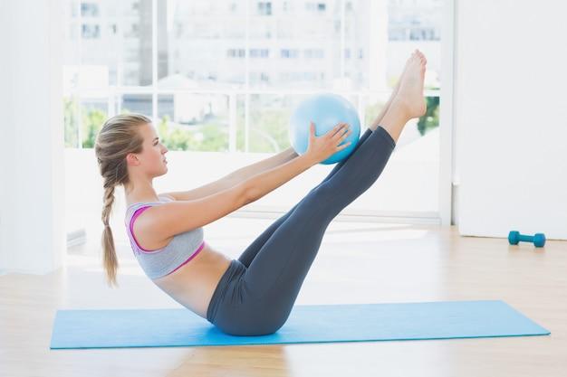 Mulher desportiva segurando uma bola no estúdio de fitness