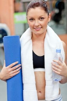 Mulher desportiva, segurando uma garrafa de água e um colchonete, olhando para a câmera
