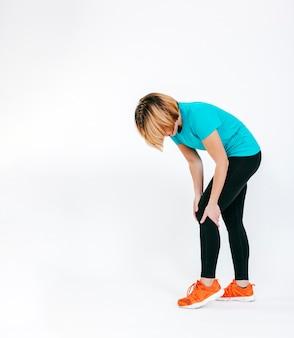 Mulher desportiva tocando joelho dolorido