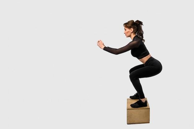 Mulher desportiva treinando, bombeando os músculos das mãos e pernas. mulher no sportswear preto. força e motivação. vista lateral