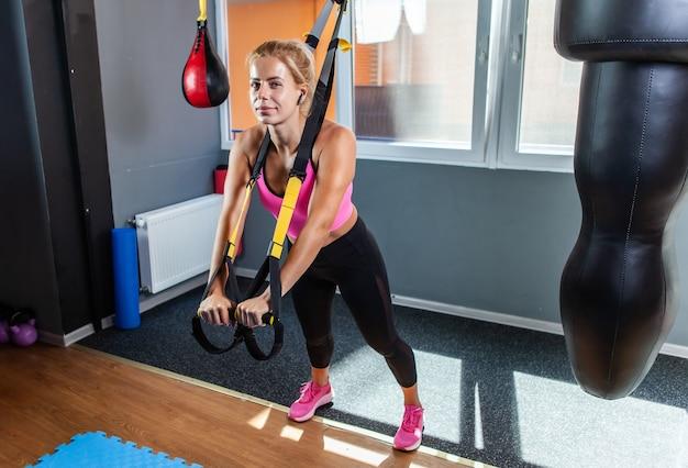 Mulher desportiva treinando com alças trx fitness na academia. bela dama exercitando seus músculos estilingue ou alças de suspensão.