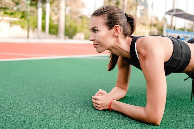 Mulher desportiva treinando e fazendo exercícios no estádio de fitness de manhã