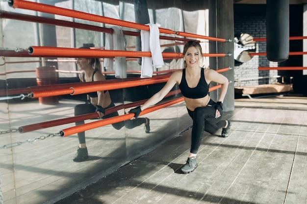 Mulher desportiva treino treino de manhã no ginásio. jovem mulher fazendo exercícios de ginástica no ginásio