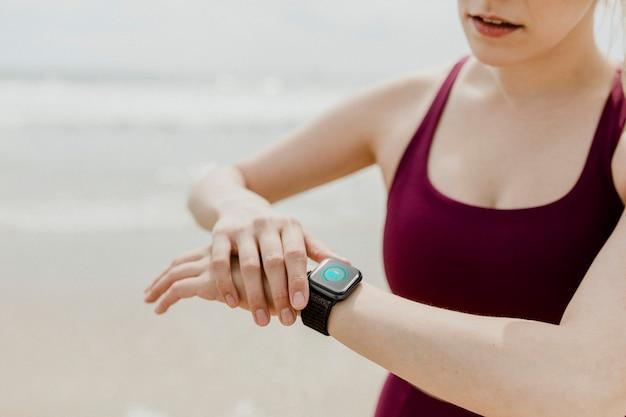 Mulher desportiva verificando o smartwatch na praia