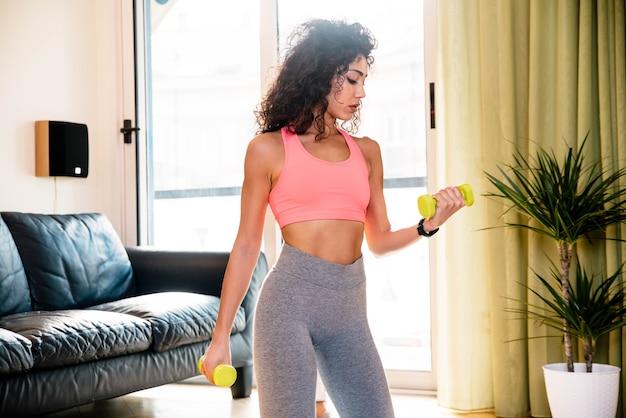 Mulher desportiva vestindo roupas esportivas e malhando em casa levantando pesos