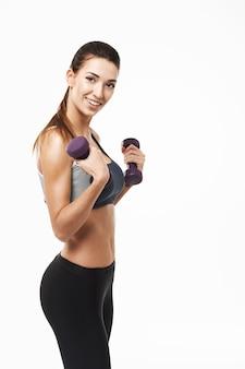 Mulher desportivo com halteres sorrindo posando em branco.