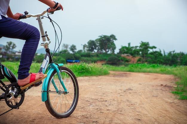 Mulher despreocupada, andar de bicicleta no parque se divertindo na tarde de verão