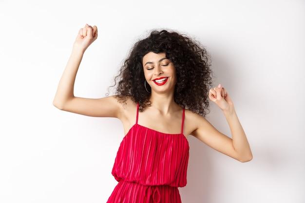 Mulher despreocupada com cabelo encaracolado, dançando na festa, usando um vestido vermelho, relaxando com música, em pé no fundo branco.